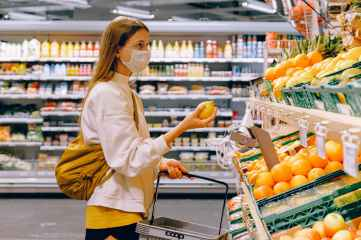 woman in yellow tshirt and beige jacket holding a fruit stand